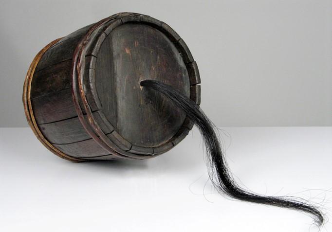 Instrument muzyczny wykonany z drewnianej beczki i końskiego włosia wychodzącego w formie długiego kosmyka z boku beczki