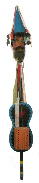 Instrument zwany diabelskimi skrzypcami. Wysoki, pionowy instrument z osadzoną na czubku drewnianą głową.