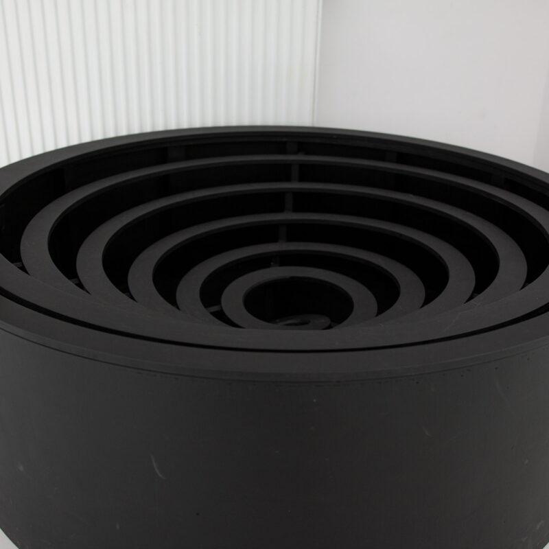 Obiekt z wystawy czarna spirala. Konkstrukcja drewniana po której można toczyć drewniane kule. Reszta pomieszczenia jasna.