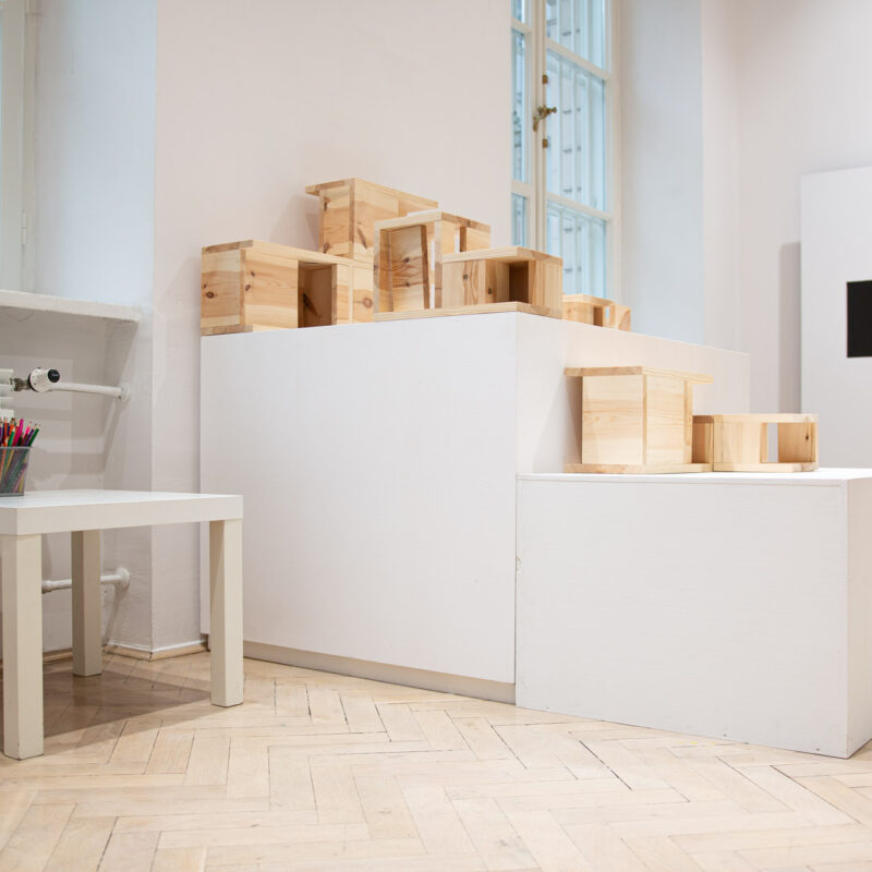 Przestrzeń wystawy, jasna, widna. Podest na nimi karmini z naturalnego drewna ustawione w kopozycji przypomiającej układ urbanistyczyny miasta.
