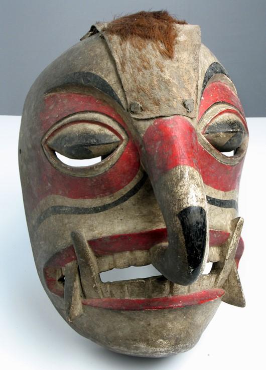 Maska rytualna drewniana wykorzystywana przez plemię Kwakiutlów. Maska pomalowana w czerwone i czarne pasy widoczne na wypłowiałym białym tle.