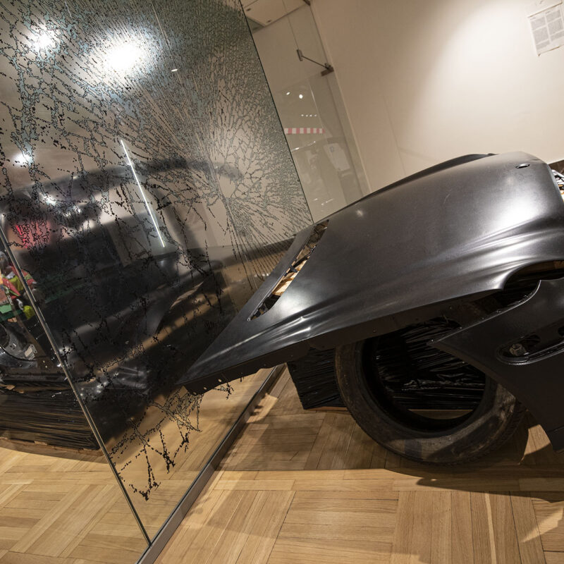 Fotografia prezentuje umieszczoną na wysokości kolan maskę samochodu oddzieloną szklanym przepierzeniem od reszty skasowanej i wybebeszonej karoserii. Na szybie przedzielającej naklejka imitująca popękaną szybę samochodową.