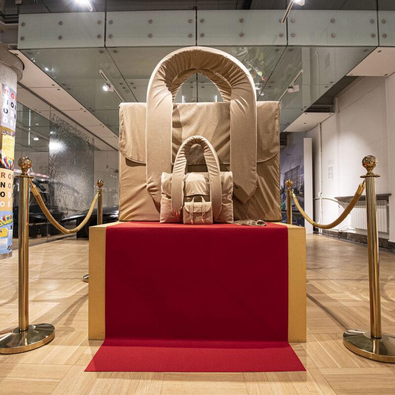 Trzy beżowe torebki stojące na 60 centymetrowym postumencie wyściełanym czerwoną tkaniną. Jedna torebka jest przeskalowana, ma ok 100 cm wysokości z ramionami, druga zwyczajnej wielkości, trzecia miniaturowa. Po dwóch stronach postumentu po dwa złote słupki połączone złotą liną.