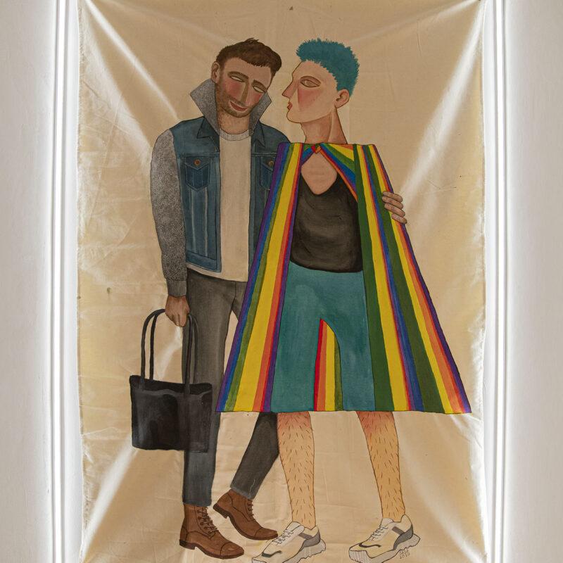 Fotografia tkaniny na której namalowane są dwie męskie postaci trzymające się w przyjacielskim/miłosnym uścisku. Postać po lewej ubrana modnie i casualowo. Ta po prawej ubrana niecodziennie: w zielone krótkie spodnie, czarną bluzkę i ponczo w paski w kolorach tęczy. Całość dopełniają włosy w kolorze spodenek.