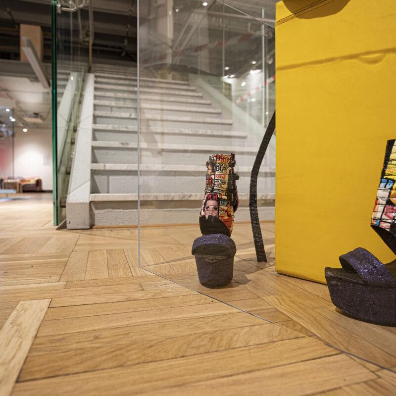 Zdjęcie przedstawia buty na bardzo wysokim obcasie, na cholewce których nadrukowane są postaci z pierwszych stron gazet modowych. Buty umieszczone są na ziemi i zamknięte w gablocie razem z żółtym sześcianem. W tle widać elementy architektoniczne pomieszczenia, gdzie znajduje się wystawa.