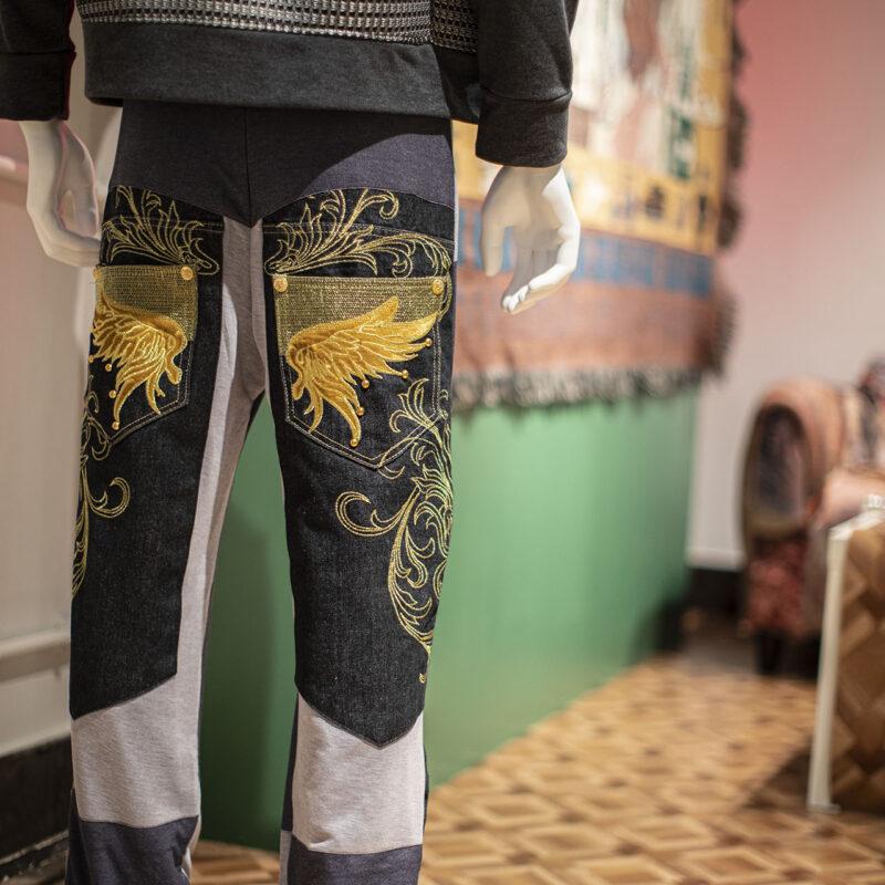 Zdjęcie manekina od tyłu do wysokości połowy pleców. Manekin ma spodnie dresowo-jeansowe z bardzo bogatymi, wyszytymi złotymi nićmi zdobieniami na nogawkach z tyłu. Zdobienia przypominają kształtami liście egzotycznych roślin.
