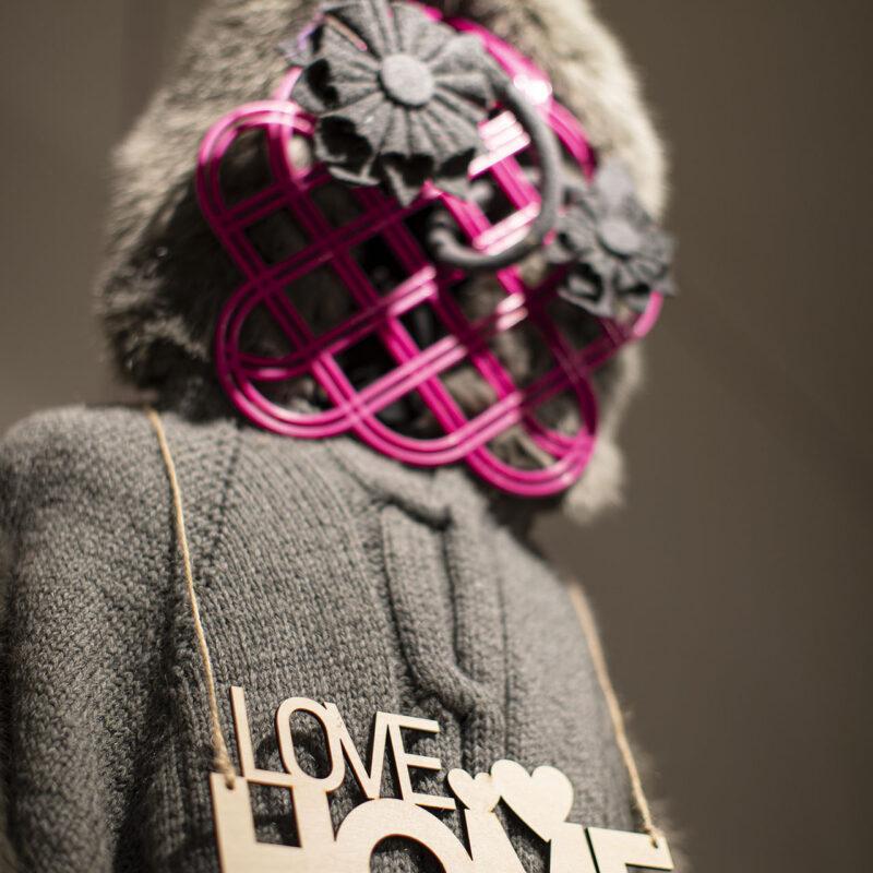 """Górna część postaci kobiecej ubranej w szary sweter, na piersi zawieszony na konopnym sznurku wycięty napis """"love home"""". Twarzy nie widać, zasłonięta jest częścią bijącą trzepaczki do dywanów w kolorze różowym, w kraty trzepaczki wplecione duże kwiaty zrobione z filcu, w kolorze szarym. Głowa postaci w futrzanej czapie."""