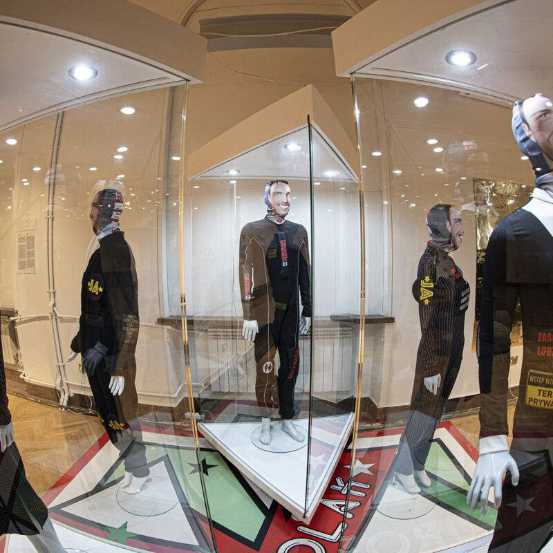 """Pięć manekinów ustawionych na bokach pięciokąta, trzy z nich znajdują się w podświetlanych gablotach szklanych. Manekiny stoją na planszy do gry Europolak (podobnej do Monopoly). Trzy manekiny kobiece i dwa męskie ubrane bardzo podobnie – w jednoczęściowe czarne kostiumy z napisami w jasnych kolorach: """"zasoby ludzkie"""", """"teren prywatny"""", """"ja"""", """"motywacja"""". Na głowach manekinów chusty z nadrukowanymi jednakowymi męskimi, uśmiechniętymi twarzami."""