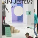 """Zdjęcie kolorowe przedstawia lustro z naklejonym u góry pytaniem """"Kim jestem?"""". Po środku lustra wycięta została okrągła dziura wielkości głowy. Pozostałą część fotografii buduje odbicie w lustrze, w którym widzimy dorosłą postać stojącą na podeście oraz dziecko bawiące się na podłodze."""