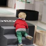 """Zdjęcie kolorowe przedstawia małego chłopca wspinającego się po schodkach na podest z napisem """"mądrość""""."""