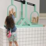 Zdjęcie kolorowe pokazuje dziewczynkę w wieku około 4 lat, która bawi się wagą. Zielona waga ustawiona jest na białej, kraciastej szafce, odważniki wykonano z drewna w kształcie walców. Poszczególne szalki oznaczone są pojęciami: mądrość, głupota. Waga chyli się ku mądrości - drewniane walce przeważają ją.