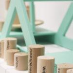 Zdjęcie przedstawia drewniane walce ustawione wzdłuż z napisami: wiedza, sprawiedliwość, świadomość, rozum.