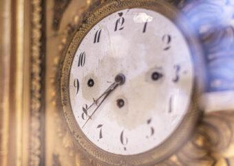 Zdjęcie kolorowe, zbliżenie na zegar ścienny prezentowany na wystawie. Zegar w kolorze złotym, tarcza biała, cyfry i wskazówki są czarne.