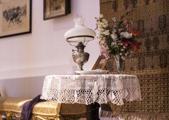 Zdjęcie kolorowe, przedstawiające fragmnet wystawy, sala druga. Kadr obejmuje drewniny stolik z białą serwetą wykonaną na szydełku, wazon z kwiatami i lampę. Obiekty XIX-wieczne.