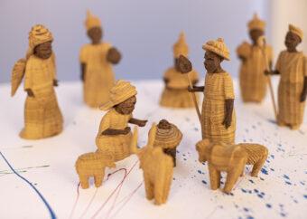 Siedem postaci ludzkich zgromadzonych wokół dziecka w beciku. Postacie wykonane z drewna. Trzy z nich w koronach. Jedna ze skrzydłami. Dodatkowo przedstawienia osła, krowy i dwóch owiec