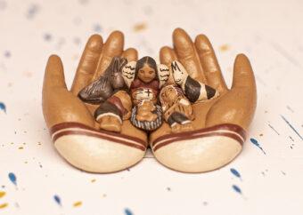 Trzy postacie ludzkie z dzieckiem umieszczone na dwu otwartych dłoniach. Dodatkowo dwa przedstawienia zwierząt