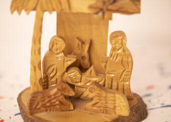 Dwie postacie ludzkie wraz z dzieckiem umieszczone na tle palmy. Dodatkowo trzy zwierzęta. Całość wykonana z jasnego drewna