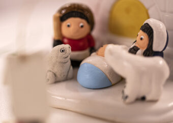 Dwie postacie ludzkie z dzieckiem na tle igloo. Postacie ubrane w stroje eskimoskie. Obok foka i biały niedźwiedź