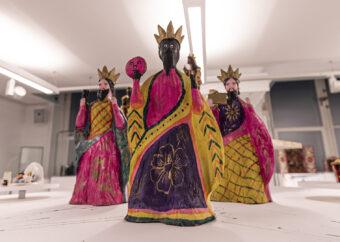 Trzy wolno stojące postacie ludzkie. Ubrane w korony w stroje utrzymane w estetyce Ameryki Południowej