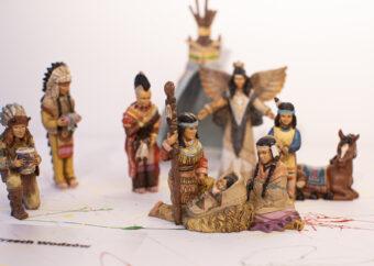 Siedem postaci ludzkich na białym tle z kolorowymi pigmentami. W tle wigwam. Postaci ubrane w stroje Indian Ameryki Północnej. Jedna z postaci ze skrzydłami. Dodatkowo leżący koń.