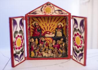 Przedstawienie wielopostaciowe umieszczone w kasetce z otwartymi drzwiczkami. W górnej partii dwie postaci ludzkie flankujące leżące w beciku dziecko na rle promieni słonecznych. W dolanej partii przedstawienie wielopostaciowe ukazujące grupę orantów z głowami wzniesionymi ku górze. Całość utrzymana w estetyce Ameryki Południowej