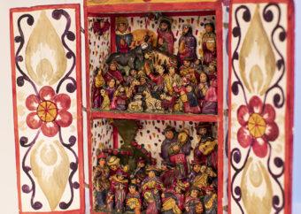Przedstawienie wielopostaciowe umieszczone w kasetce z otwartymi drzwiczkami. Postaci ludzkie umieszczone na dwóch poziomach. W górnej partii wiele postaci wraz ze zwierzętami. W dolnej partii muzycy na tle kaktusa. Postacie ubrane w stroje Meksykańskie