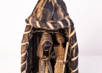 Dwie stojące postaci ludzkie z leżącym na ziemi dzieckiem umieszczone w ciemnym namiocie. Całość wykonana z drewna oraz liści traw.