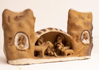 Dwie postacie ludzkie z leżącym dzieckiem w towarzystwie czterech zwierząt. Postaci umieszczone w budynku flankowanym przez dwie wieżyczki. Całość wykonana z jasnej gliny