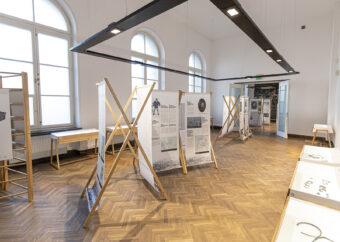 Zdjęcie kolorowe prezentujące wnętrze wystawy, sala pierwsza. Widok na ekspozytory zbudowane z drewnianych listewek i przymocowanych do nich banerów. Na banerach wydrukowane są informacje o mieście Vilaka i poszczególnych, znanych mieszkańcach.