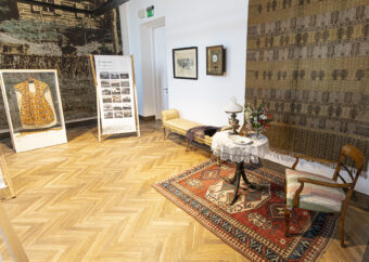 Zdjęcie kolorowe prezentujące wnętrze drugij sali wystawy. Na zdjęciu widoczne są: gablota z szatami, bander ze archiwalnymi zdjęciami miejscowości Vilaka, oraz kącik z przedmiotami: mała sofa, stolik, krzesło, lampa. Obiekty XIX-wieczne.