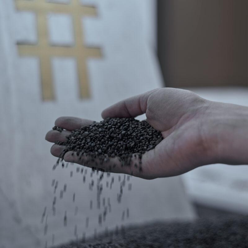 Na pierwszym planie dłoń z drobnym żwirem wielkości grudek kawy rozpuszczalnej. Grudki w kolorze grafitowym. Tło nieczytelne. Fot Maciej Jędrzejewski