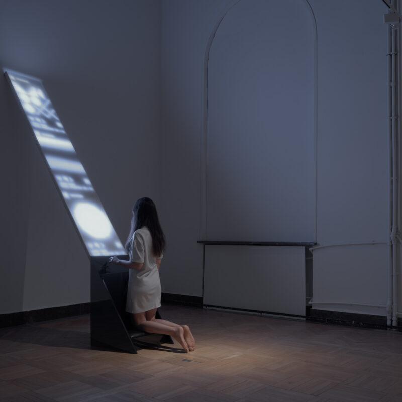 Zdjęcie przedstawia kobietę w białej sukience klęczącą na czarnym klęczniku, z którego ukośnie w górę wychodzi długi świecący ekran. Kobieta wpatruje się w wyświetlacz. Na wyświetlaczu nieczytelne jaśniejsze plamy. Tło zdjęcia ciemne, przedstawia narożnik dużego pomieszczenia z białymi ścianami. Fot Maciej Jędrzejewski