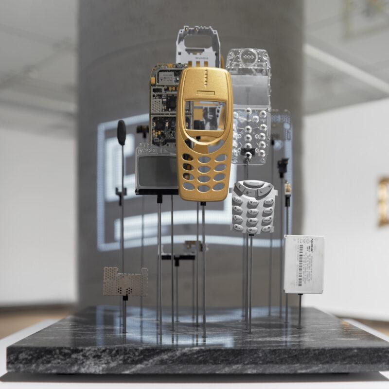 Zbliżenie, postumentu z cienkiej płyty marmurowej, w której umieszczone są sterczące pręty, na końcach których widać części telefonu komórkowego Nokia 3310. Na pierwszym planie złota obudowa telefonu, po prawej klawiatura telefonu, bateria. Po lewej od obudowy telefonu widać ekranik, i płytę główną telefonu. Tło nieczytelne. Fot Maciej Jędrzejewski