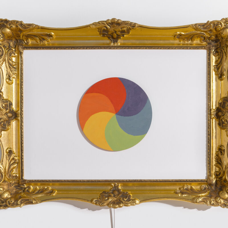 Złota, bardzo bogato zdobiona rama obrazu, , wewnątrz białe tło. Na środku tła koło pomalowane w sześciu kolorach: ciemnoniebieskim, niebieskim, zielonym, żółtym, pomarańczowym i czerwonym. Fot Maciej Jędrzejewski