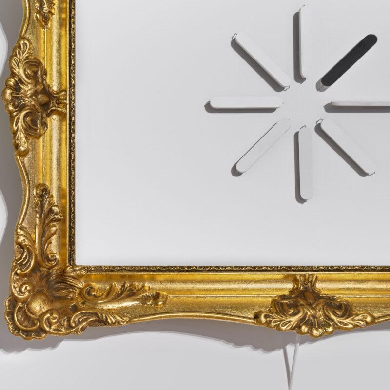 Fragment złotej, dekoracyjnej (barokowej) ramy obrazu, a wewnątrz ośmioramienna gwiazda. Ramiona w kształcie cienkich szpatułek. Ta w prawym górnym rogu zdjęcia, umiejscowiona na przekątnej fotografii jest czarna. Następna jest jakby obrócona cieńszym bokiem szpatułki. Fot Maciej Jędrzejewski