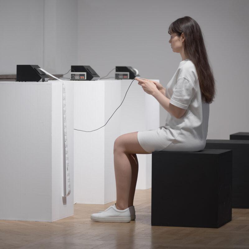 Kobieta w białej sukience siedzi na czarnym sześcianie foremnym. Trzyma w ręce kontroler do gry , który kablem połączony jest z graniastym czarnym pudełkiem stojącym przed nią na dość wysokim białym postumencie. Z pudełka zwisa rozwinięta wstęga papieru. W tle widać jeszcze dwa takie pudełka stojące na białych postumentach z małymi szarymi prostokątami na bokach. Fot Maciej Jędrzejewski