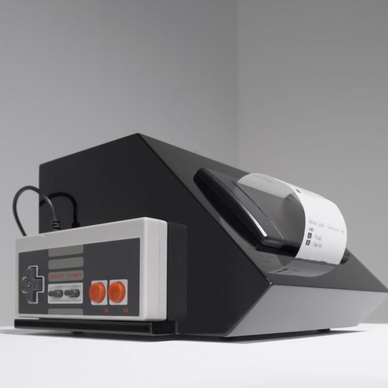 Zbliżenie na przedmiot: graniaste, czarne pudełko, z którego wychodzi kawałek paragonu. Z boku pudełka umieszczony jest jasnoszary prostokąt z dwoma czerwonymi guzikami po jego prawej stronie, dwoma szarymi w środku i krzyżykiem po lewej. Z górnej krawędzi wychodzi kabelek – jest to pad do starej gry Nintendo.Fot Maciej Jędrzejewski