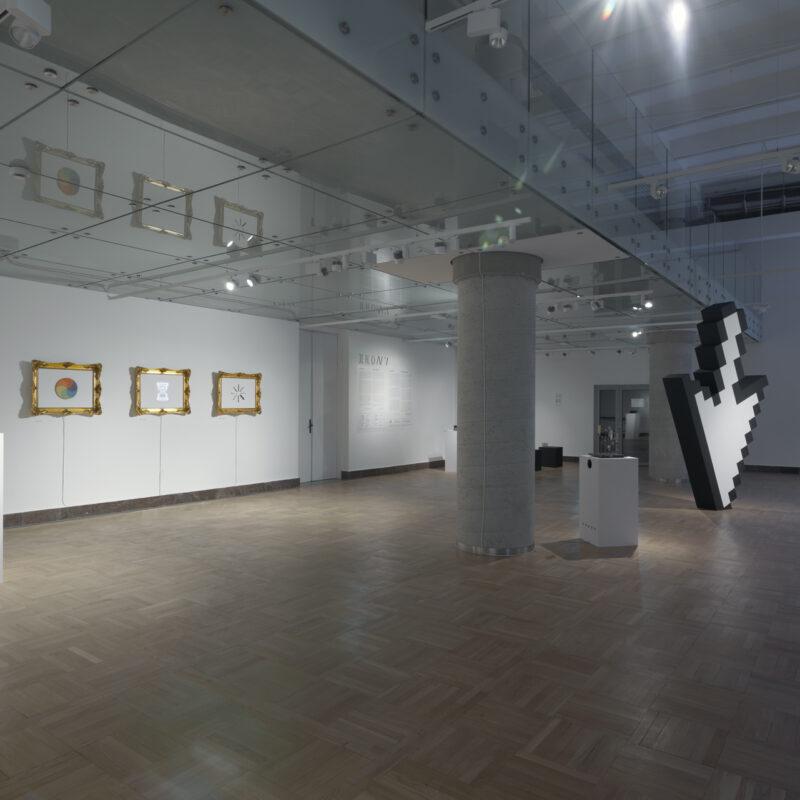 Widok ogólny przestronnego pomieszczenia. Na podłodze drewniany parkiet, w centrum kolumna, po jej prawej stronie mały biały sześcian, jeszcze bliżej lewej krawędzi ogromna strzałka kursora skierowana grotem w kierunku podłogi. Po lewej od kolumny widok na ścianę, na której wiszą trzy obrazy w złotych ramach. W ramie od lewej krawędzi zdjęcia tęczowe kółko, w środku klepsydra, ostatni obraz nieczytelny. Fot Maciej Jędrzejewski