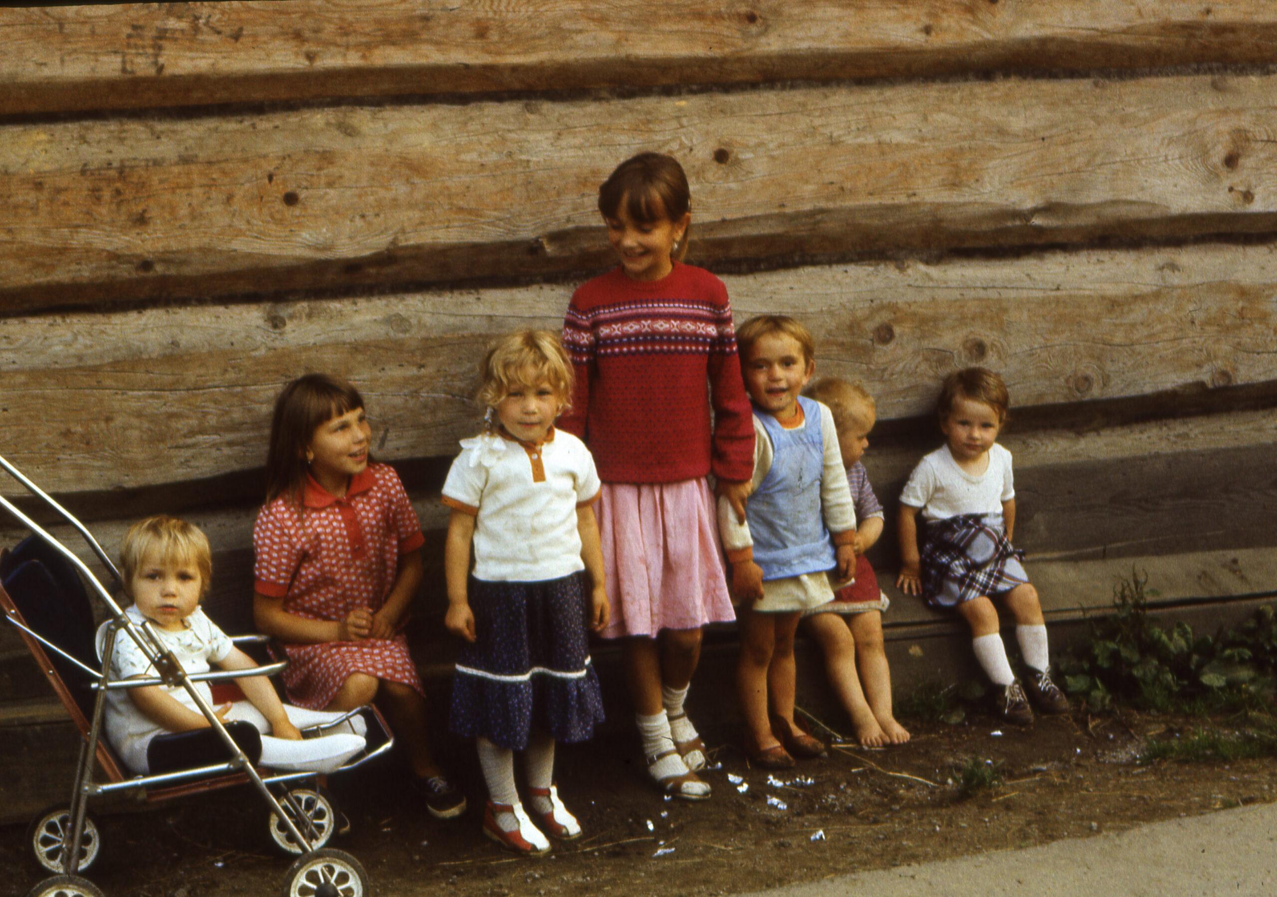 Zdjęcie kolorowe. Dzieci mieszkające na wsi, na tle drewnianej ściany. Liczba dzieci: siedmioro. Wiek dzieci: od roku do 10 lat.