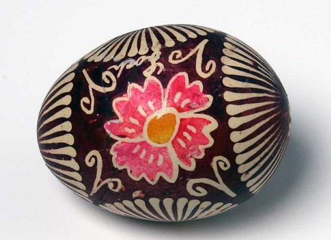 Pisanka batikowa, barwiona na ciemny koloror, dekoracje jasne, centralnie rysunek kwiatu.