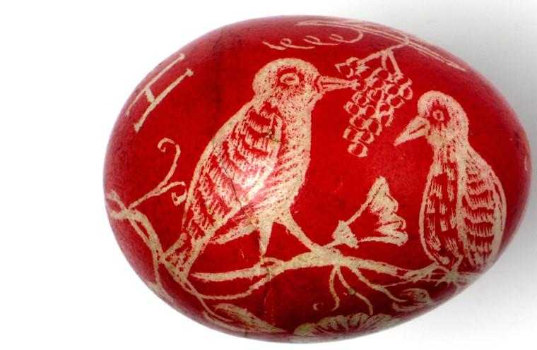 Pisanka rytowniczka barwiona na czerwono, wydrapano na niej wizerunek ptaszków na gałęzi.