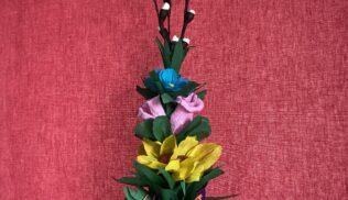 Na ciemno różowym tle znajduje się palma wielkanocna wykonana z bibuły. Od dołu dostrzegalne są zielone bibułowe liście, powyżej fioletowe, żółte, różowe i niebieskie kwiaty z tego samego materiału, zaś na szczycie palemki widoczne są gałązki bazi.