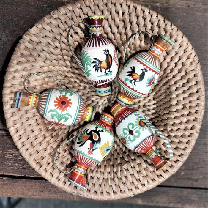 Zdjęcie kolorowowe, przedstawiające płaskie plecione naczynie z pisankami ozdobionymi wycianankami. Dodane ozdoby sprawiają wrażenie, że pisanki są małymi dzbaneczkami: z uszkiem do trzymania i dziubkiem. Ozdoby z papieru.