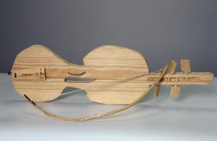 Zdjęcie przedstawia proste skrzypce na płaskiej desce drewnianej ze smykiem, wykonane w roku 2010