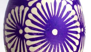 Zdjęcie kolorowe przedstawiające pisankę wielkanocną tworzoną metodą batikową. Jajko barwione na fioletowo z ozdobnymi okręgami imitującymi kwiaty znajduje się na białym tle.