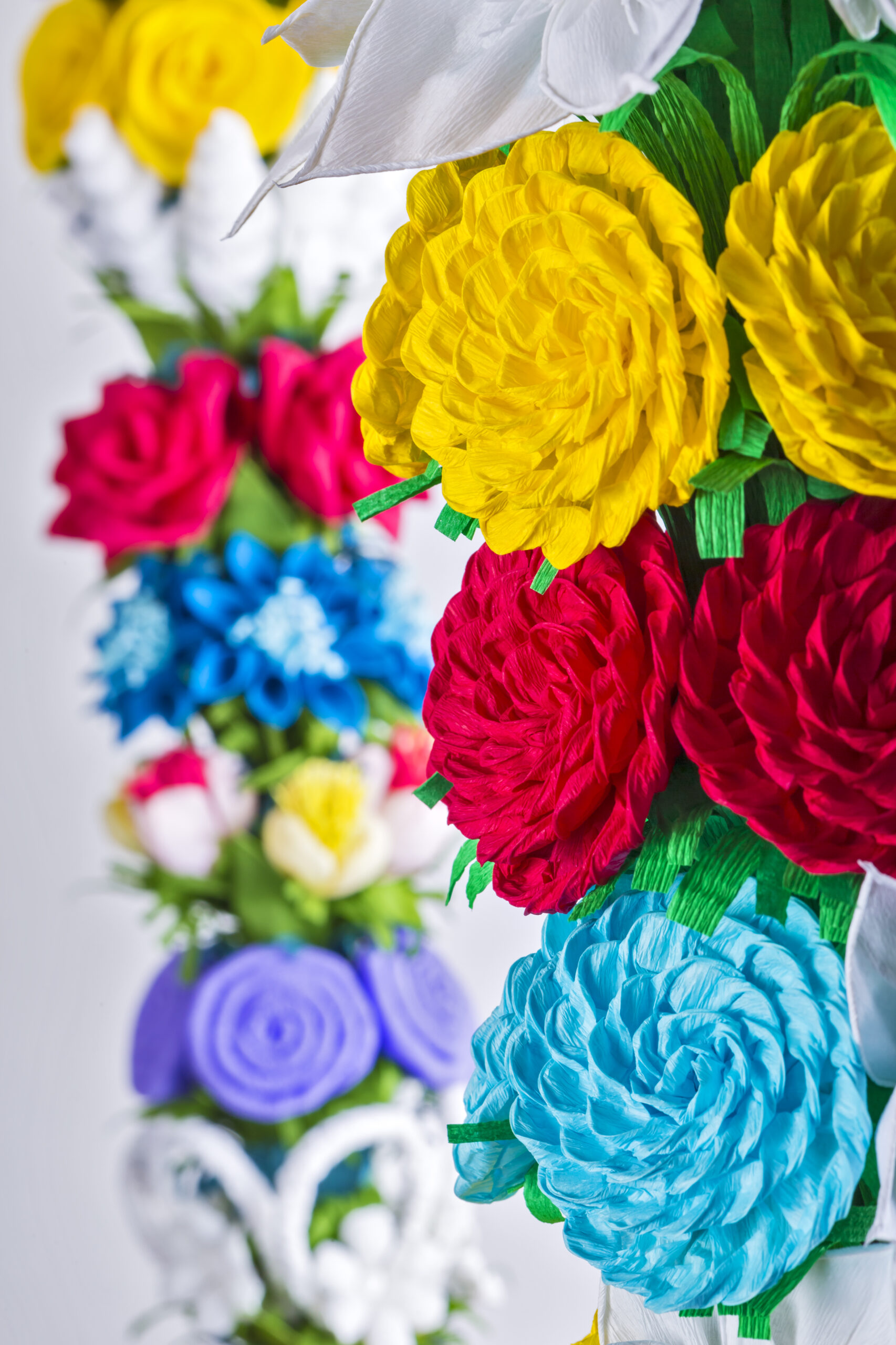 Zdjęcie przedstawia dwie palemki kurpiowskie. Wykonane z krepiny wielokoloworowe kwiaty okalają trzon plemki.