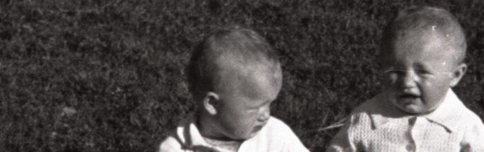 Zdjęcie czarno-białe. W kadrze widoczne główy dwójki dzieci w wieku około 8 miesięcy/