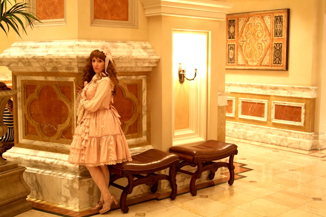 Na zdjęciu widac kobietę ubranaą w tylu kawaii stojącą w eleganckim pomieszczeniu.