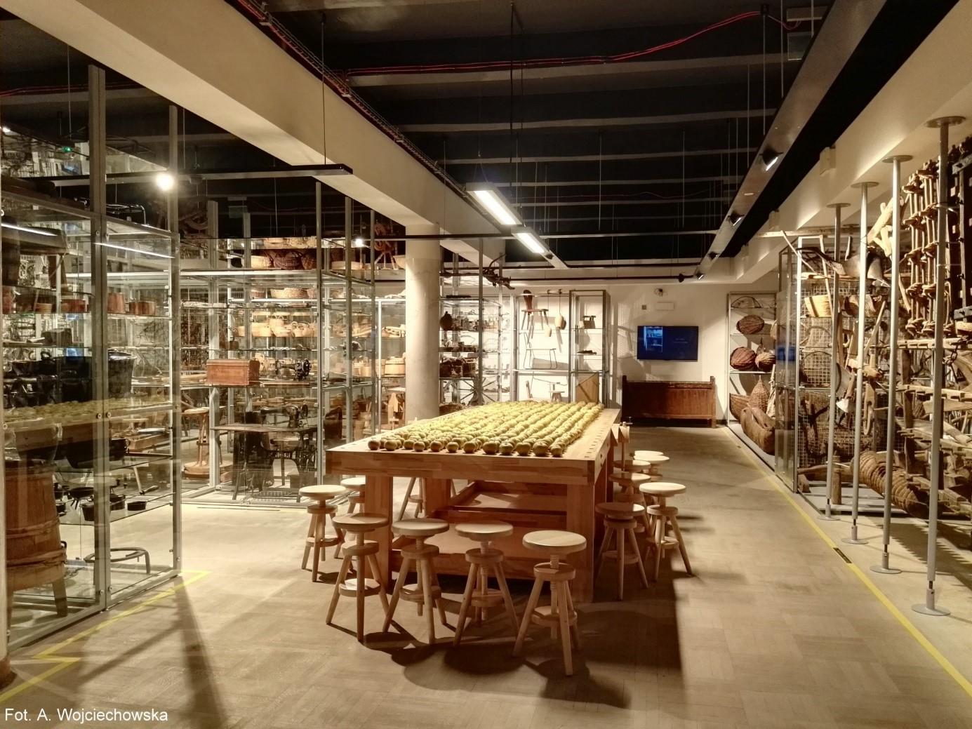 """Na fotografii duży stół wykonany z drewna klejonego, przypominający stół stolarski, oraz stołki kręcone, w przestrzeni wystawy """"Porządek rzeczy""""."""