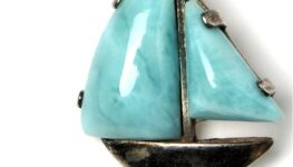Wisior w kształecie żaglowca. Żagiel z niebieskiego kamienia, maszt i kadłub ze stopu metali.